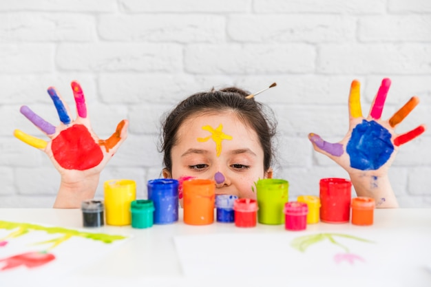 Girl looking at multicolored paint bottles on the white desk with her painted palms