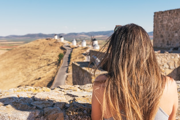 Girl looking at old windmills in spain