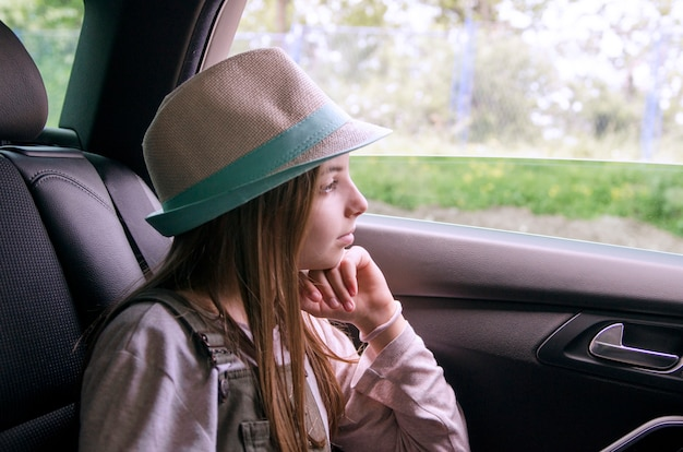 Girl looking out car window during the weekend trip.child girl traveling to village, looking at view from inside the car