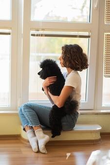 Девушка смотрит на улицу со своей собакой во время карантина