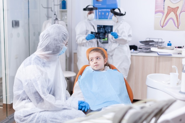 Girl looking pensive mother sitting on dental chair wearing coverall because of coronavirus outbreak. stomatologist during covid19 wearing ppe suit doing teeth procedure of child sitting on chair.