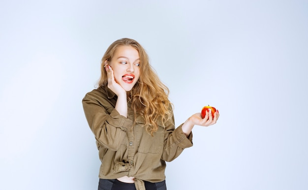 Girl looking to a red peach with appetite.