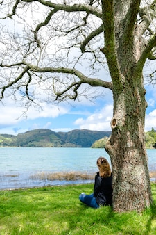 Girl looking over sete cidades lake into the mountains, azores, portugal.
