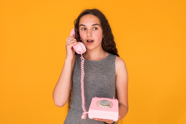 Girl looking shocked while talking on the telephone