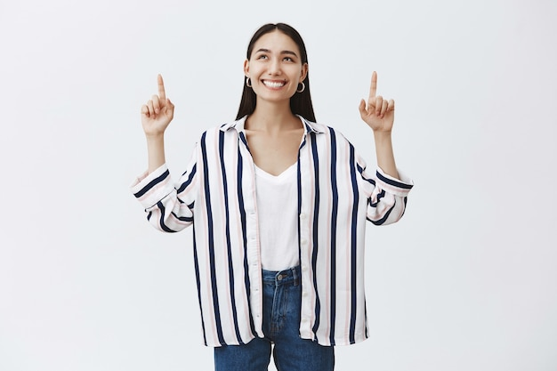 Girl looking at sky enjoying warm sunny weather. attractive carefree female student in striped blouse and jeans, looking and pointing up with broad happy smile, standing over gray wall