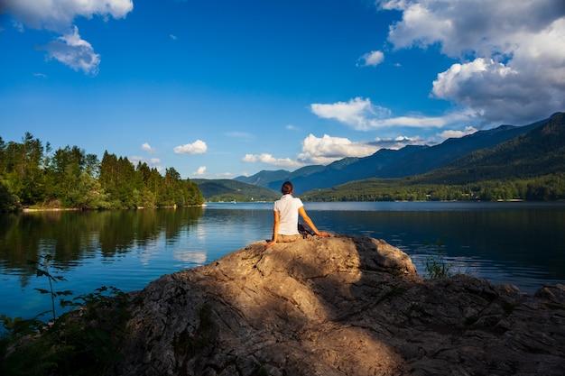 Девушка смотрит живописное озеро бохинь