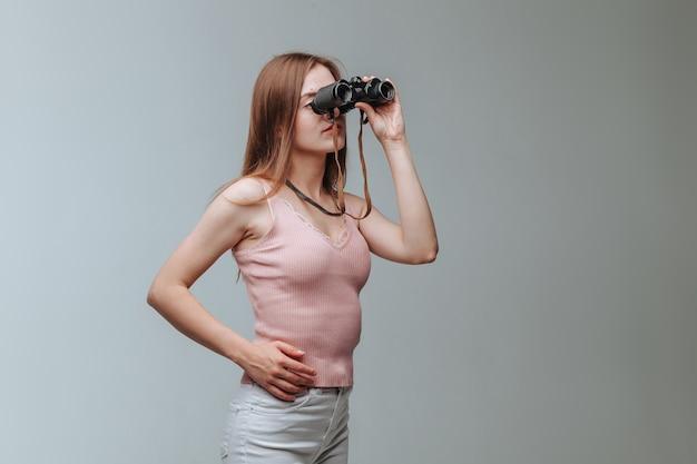 회색 배경에 쌍안경을 통해 보는 여자