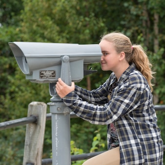 Girl looking through a coin-operated binoculars, joey's lookout, gambo, newfoundland and labrador, c