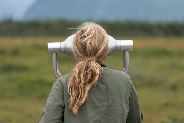 Girl looking through a coin-operated binoculars, western brook pond, norris point, gros morne nation