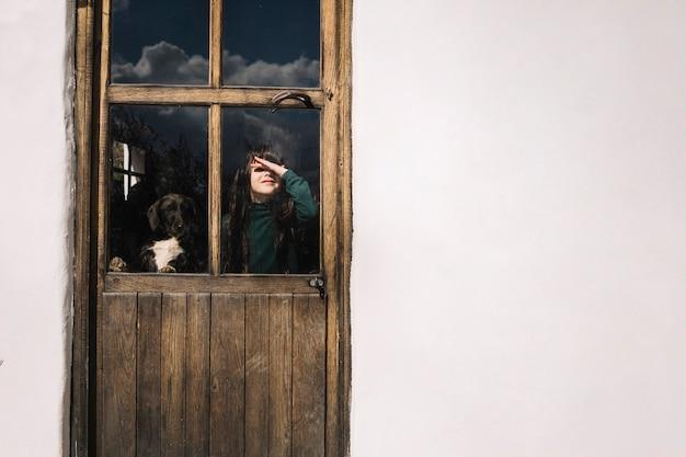 Girl looking through glass door