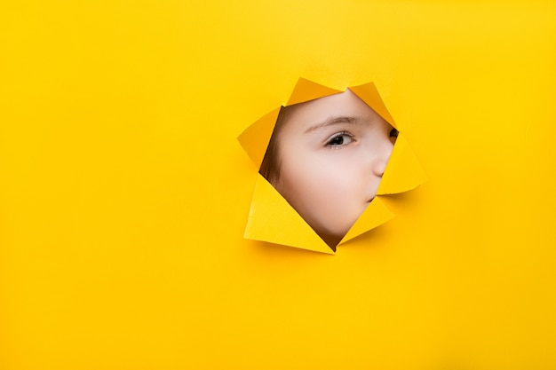 Girl looking through a hole in colored paper