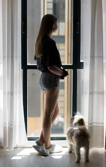 그녀의 애완 동물 옆 창문을 통해 보는 여자