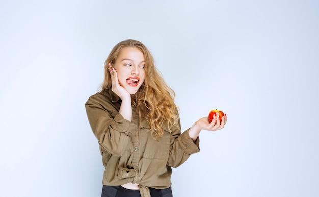 Девушка смотрит на красный персик с аппетитом.