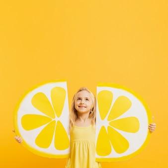 Девушка смотря вверх пока держащ украшения кусков лимона