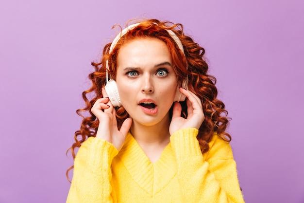 女の子は紫色の壁にショックを受けた正面を見る