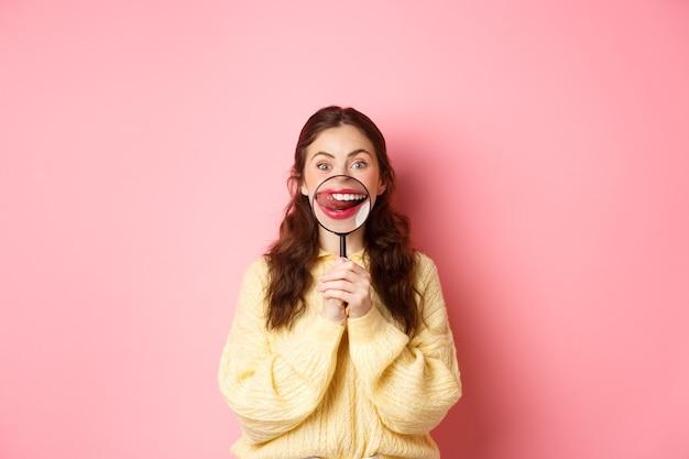 소녀는 맛있는 것을 본다. 젊은 여자는 분홍색 벽에 서서 맛있는 음식을 쳐다보고 입술을 핥는 돋보기로 입술과 유혹의 미소를 보여줍니다.
