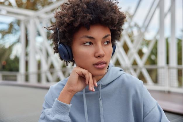 Girl looks away being deep in thoughts listens audio track via headphones dressed in hoodie poses outside