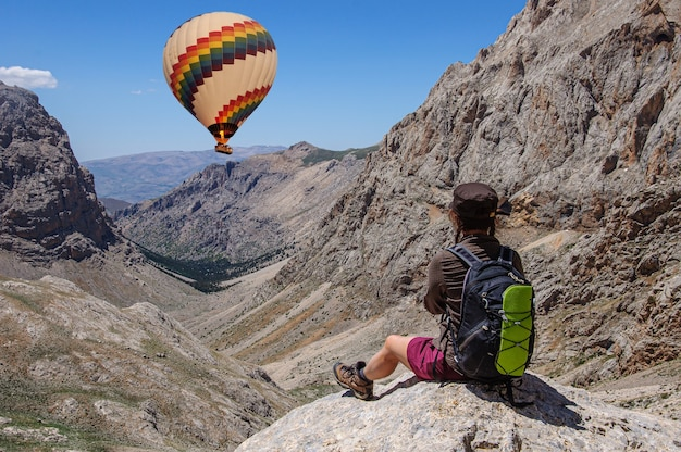 A girl looks at a bright hot air balloon in a beautiful valley of turkey