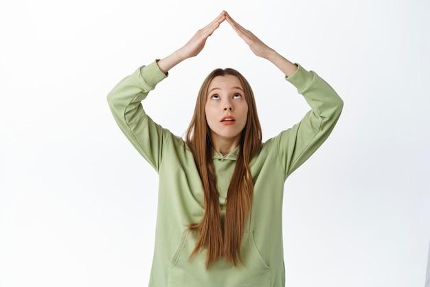 소녀는 옥상 제스처를 하는 손에 호기심을 갖고, 머리 위에 지붕 표지판을 보여주고, 하얀 벽에 후드티를 입고 서 있는 꼭대기를 쳐다보고 있습니다.