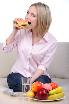 The girl looks at a healthy meal and eats a hamburger.