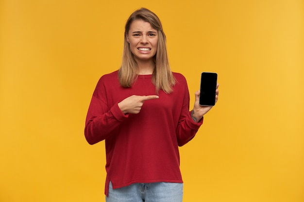 Girl looks looks with disgust, frowns, mouth opened, keeps mobile phone in her hand, black screen turned to the camera, points on it with index finger