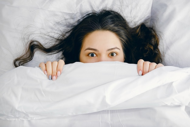 Девушка выглядывает из-под одеяла