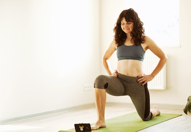 The girl looks at the phone and does a workout at home -young woman lunges in on a sports mat -