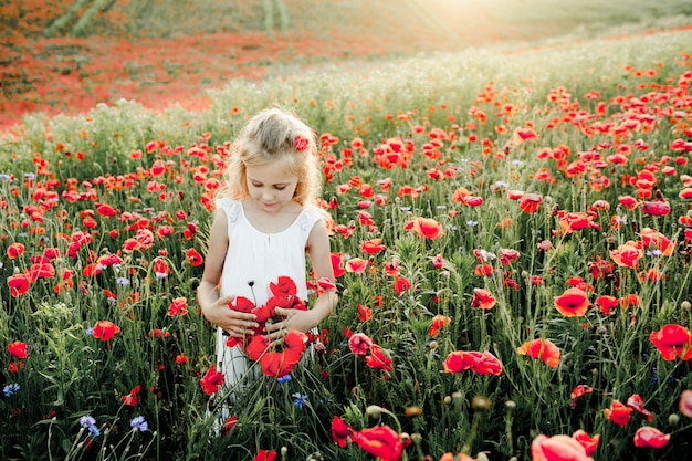 Girl looks at poppy flowers