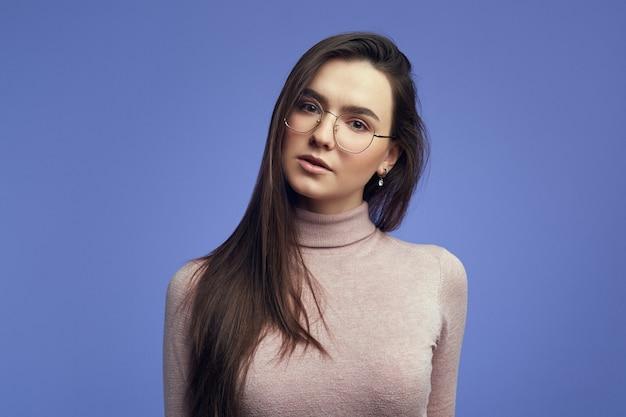 Девушка серьезно смотрит в камеру в круглых очках на фоне фиолетовой стены