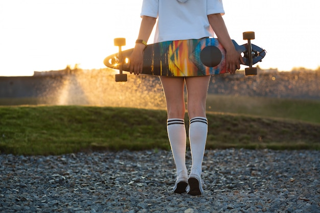 Girl looks at sunset holding a longboard in her hand