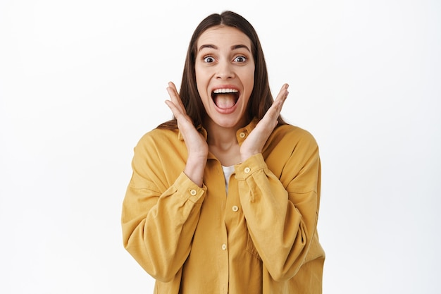 Girl looks at surprise with disbelief and happiness, shouts with joy and excitement, screaming joyful at awesome great news, checking out something amazing, standing over white wall