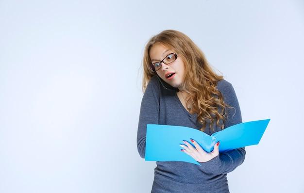 Девушка выглядит удивленной, пока разговаривает по телефону и проверяет отчеты.