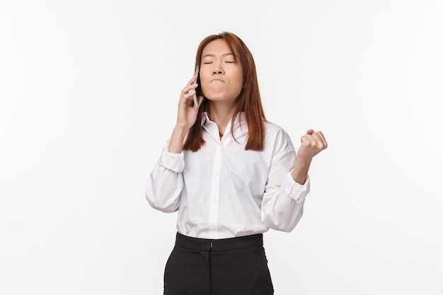 Girl losing her patience trying calm down as feeling angry and annoyed, clench fist bothered, grimacing suck lips from irritation, close eyes, having phone conversation,