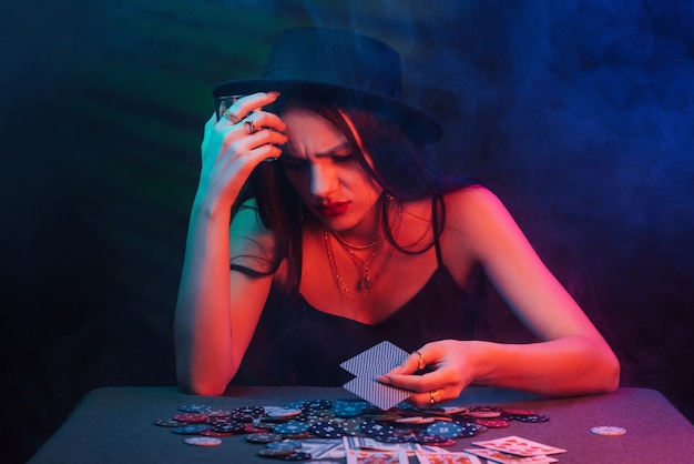 Girl lost in the casino at the table with chips and cards. the concept of failure in gambling