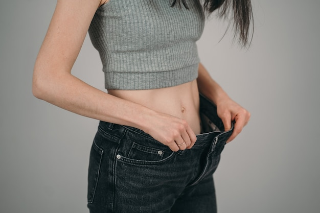 The girl lost a lot of weight. anerexia in a girl. too big jeans for a skinny girl.