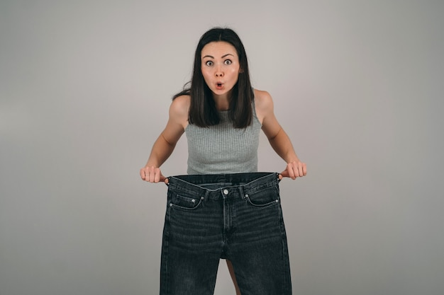 The girl lost a lot of weight. the girl is holding very large jeans. the woman is surprised how she lost weight. problems of female anorexia.