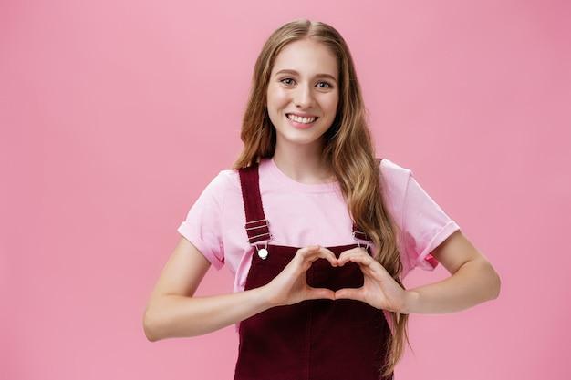 女の子は家族が大好きです。腕に小さなタトゥーがあり、体にハートのジェスチャーを示し、ピンクの壁に優しくてかわいい態度を表現するカメラで素敵な笑顔をしているオーバーオールの親切な魅力的な若い女性。
