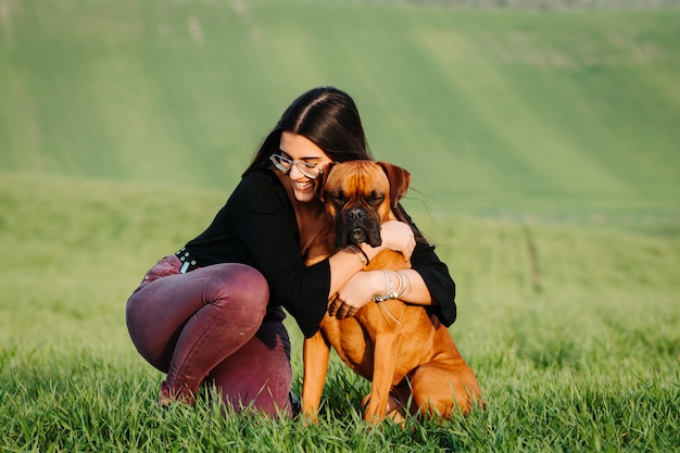Girl loving her boxer dog in the green meadow