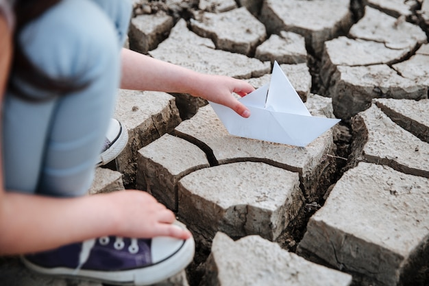 The girl lowers the paper boat onto the dry, cracked ground.