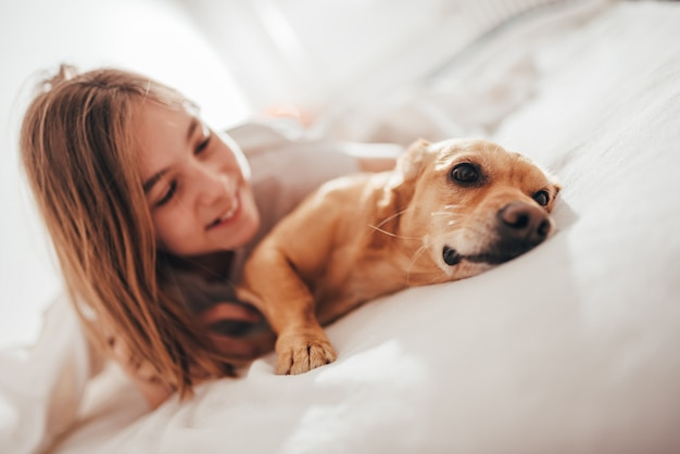 Girl lying in the bed and embracing dog