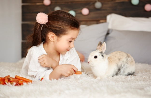 Girl lying on the bed and feeding the rabbit