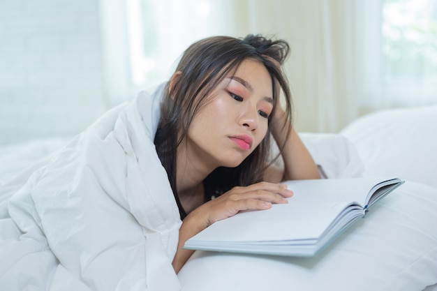 The girl lying in bed listening to music and reading books.
