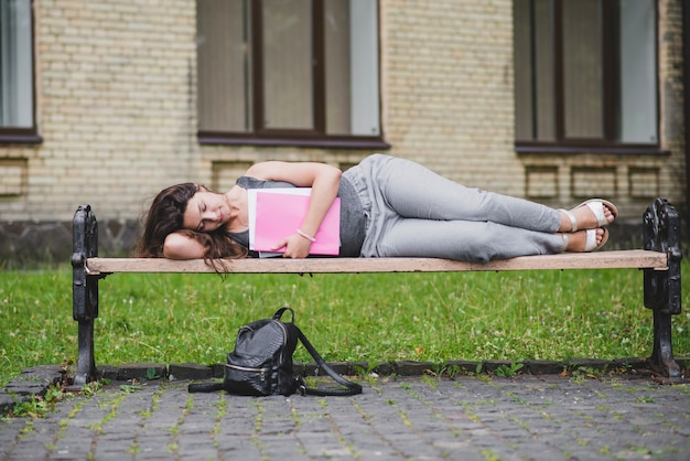 Girl lying on bench holding card board