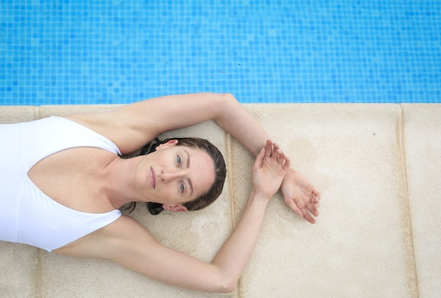 Девушка лежит на выступе бассейна