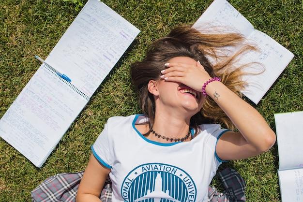 Girl lying on grass covering face