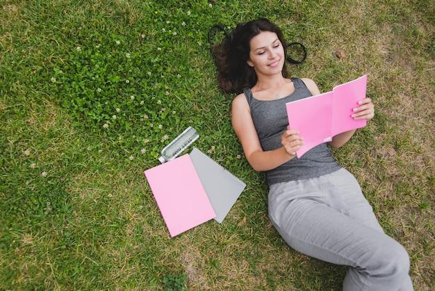 Ragazza sdraiata sul taccuino di lettura dell'erba