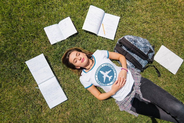 Girl lying on grass surrounded by notebooks