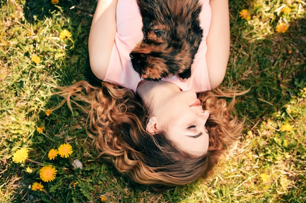 Girl lying on grass with cat on chest. spring or summer warm weather concept.
