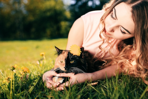 Girl lying on grass with cat. spring or summer warm weather concept.