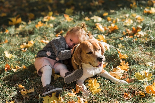 Girl lying on her beagle dog at park